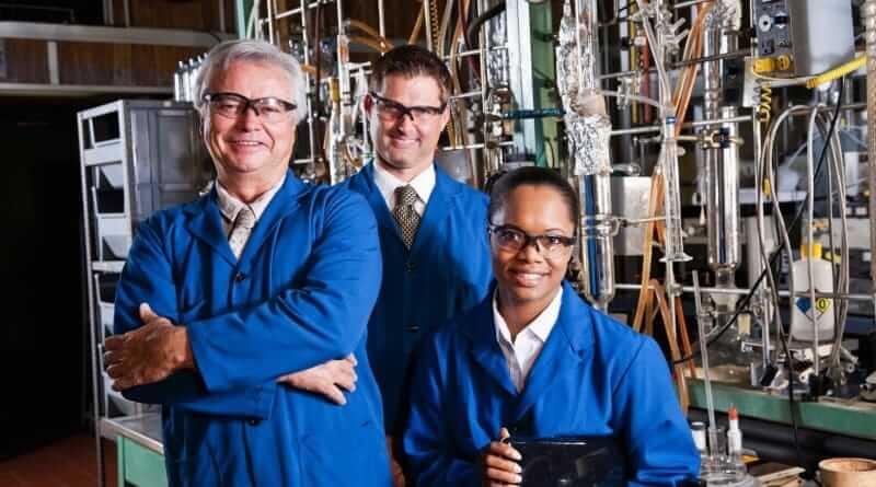 Ingenieure in blauer Schutzkleidung vor einer technischen Großanlage