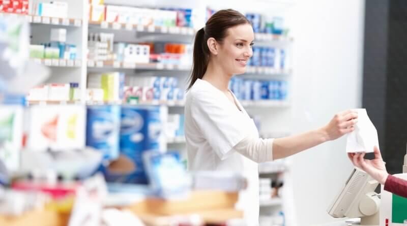 Eine junge Apothekerin in einer Apotheke beim bedienen eines Kunden