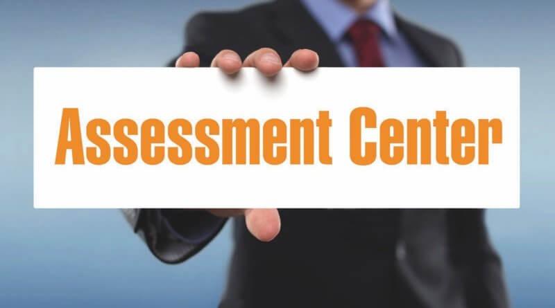 """Ein Herr im Anzug hält ein Schild mit den Worten """"Assessment Center"""" in die Kamera"""