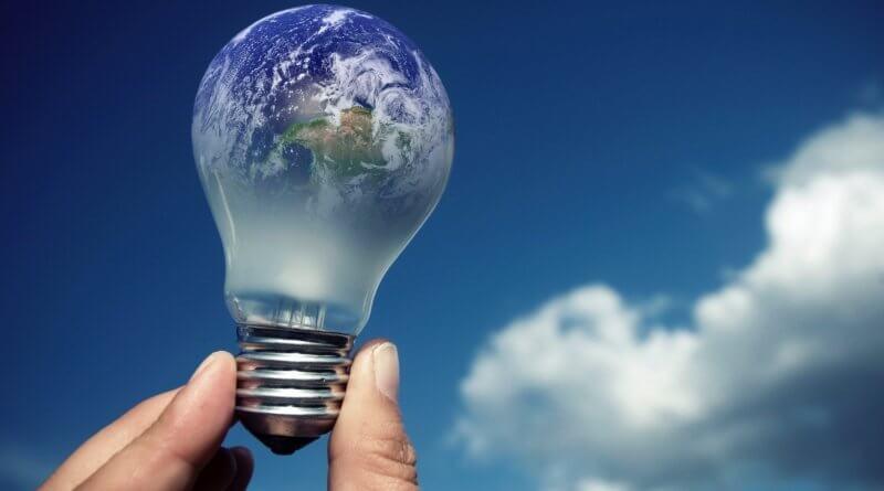 Eine Hand hält eine Glühbirne vor dem Himmel mit Wolken. Diese Glühbirne spiegelt die Erdoberfläche wider
