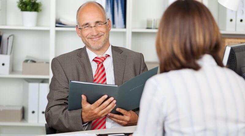 Der Recruiter mustert die Bewerbungmappe der Bewerberin, die vor ihm sitzt