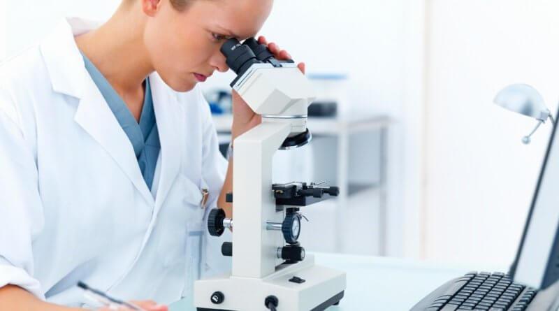 Eine junge technische Assistenin in einem Labor schaut durch ein Mikroskop während sie Notizen macht
