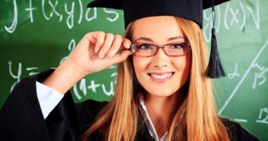 Ein graduiertes Mädchen im Graduiertenkostüm vor einer Tafel