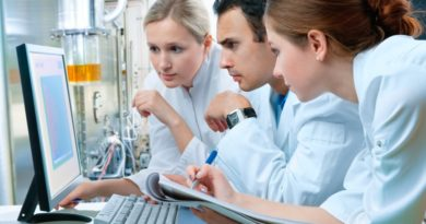 Wissenschaftler betrachten in Kitteln einen Computerbildschirm