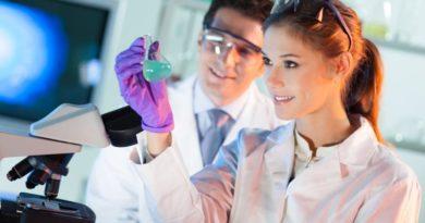 Medizinstudentin sieht sich den Inhalt eines Erlenmeyerkolbens im Labor an