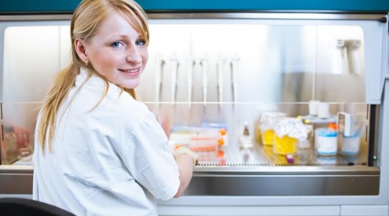 Eine Praktikanten im Bereich Wissenschaften im Labor mit Reagenzgläsern