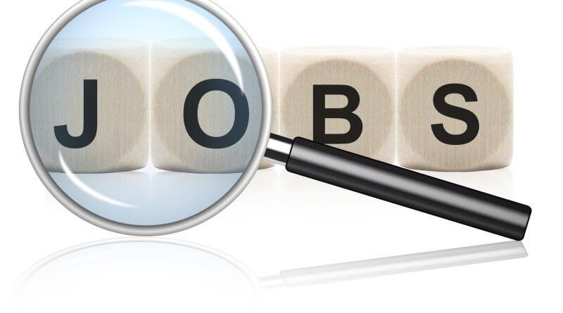 Eine Lupe untersucht das Wort Jobs. Jeder Buchstabe des Wortes
