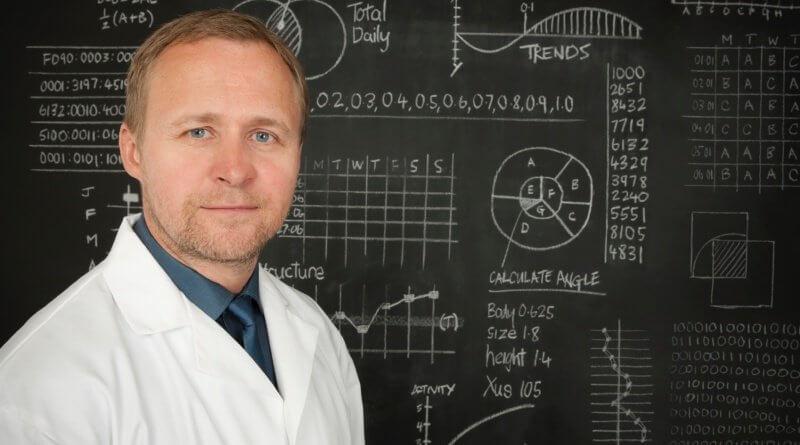 Mathematikprofessor vor einer Tafel mit Berechnungen