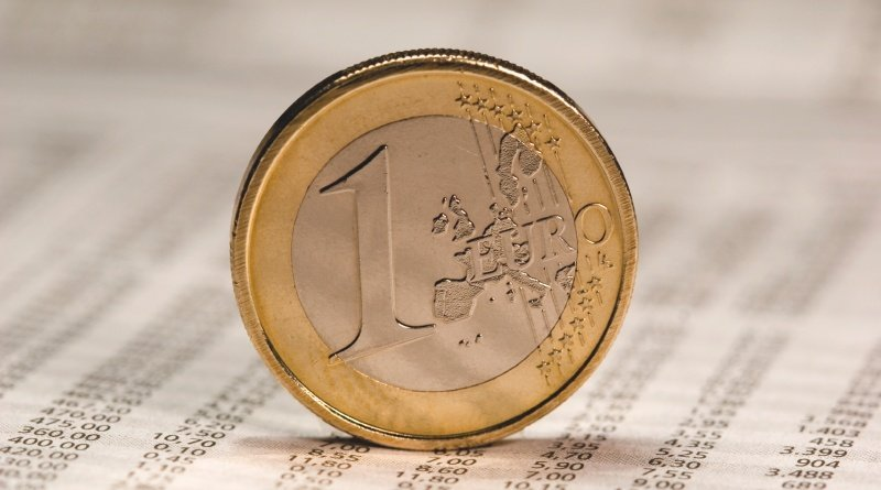 Eine 1 Euro Münze balanciert auf einem Blatt mit Zahlen