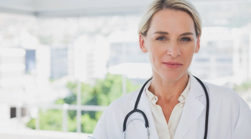 Blonde Ärztin mittleren Alters mit Stehtoskop und Arztkittel