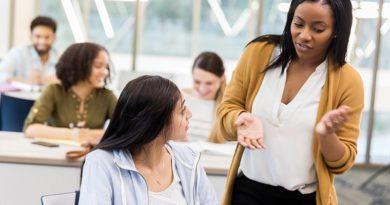 Professorin an der Fachhochschule hilft einer Schülerin bei einer Aufgabe