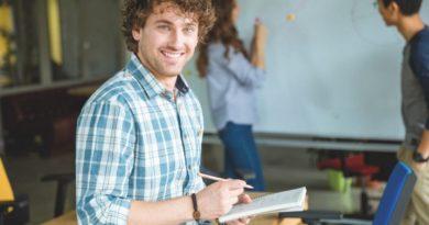 Ein fröhlicher junger ITler mit einem Notzibuch und Stift in seinen Händen. Er befindet sich in einem Seminarraum mit anderen Studenten