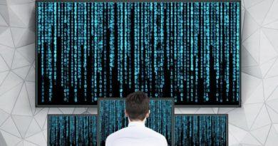 Ein Mathematiker vor mehreren Bildschirmen mit Codes im Matrix-Style