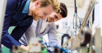 Zwei junge Ingenieure beim Arbeiten mit elektronischen Komponenten reparieren von defekten Chips