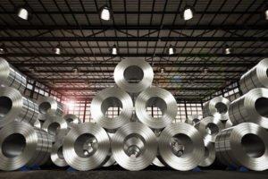 Stahlcoils, aufgeschichtet zu einer Pyramide in einer großen Lagerhalle. Rohmaterial für Anwendungsentwickler.